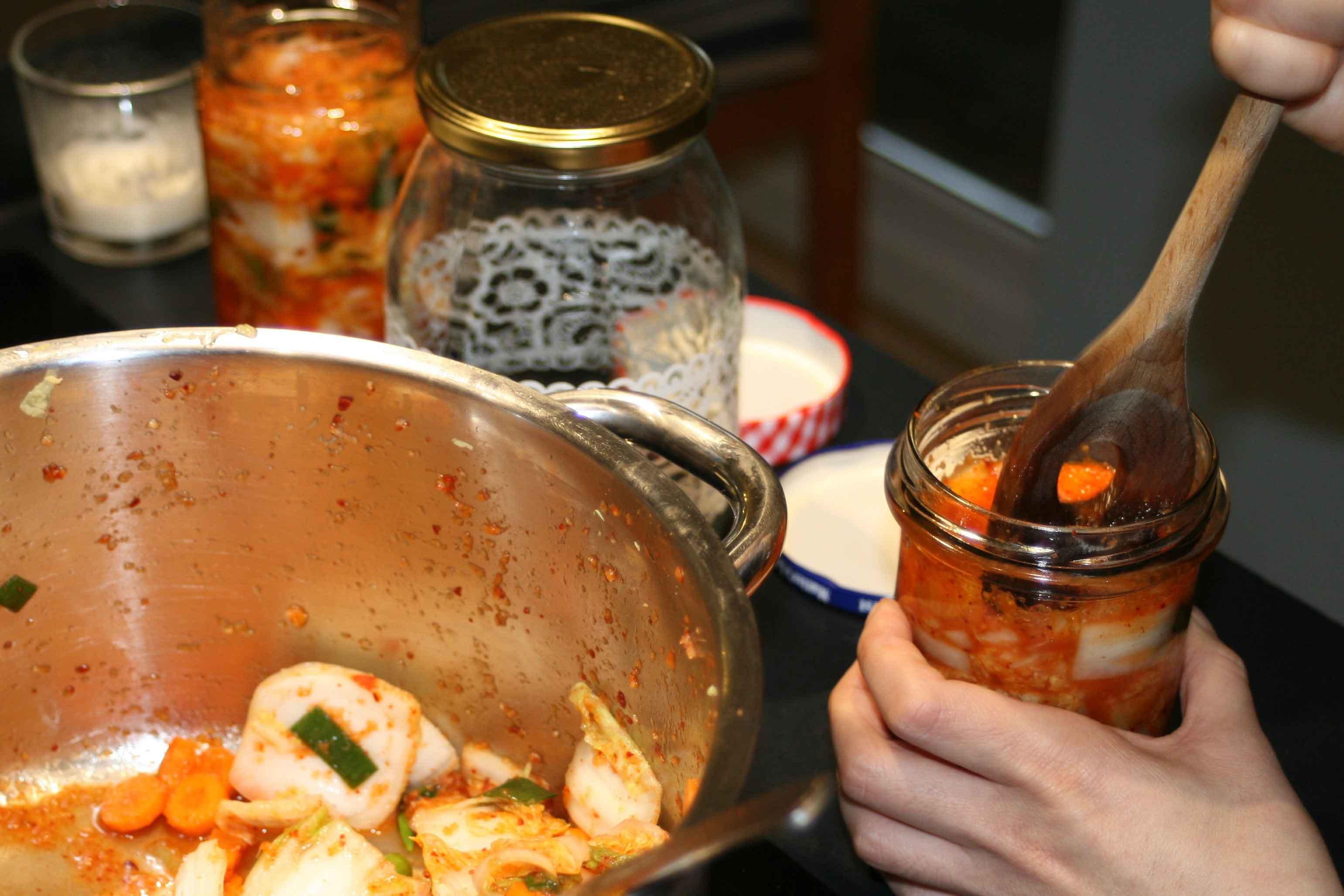 Einweggläser werden mit Kimchi gefüllt